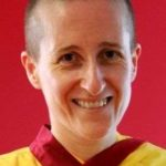 A headshot of a Buddhist nun in yellow and red ornate traditional clothing against a red backdrop